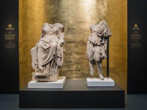 Zwei Marmorstatuen vor goldener Nische in der Ausstellung