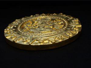 Aztekischer Kalenderstein mit Blattgold vergoldet, seitlich, vor schwarzem Hintergrund