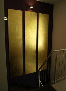 Drei vergoldete Leinwände hängend im Treppenaufgang. Blick von oben