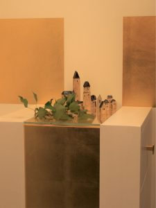 Weiße Stele mit goldenem Streifen, darauf stehen mehrere kleine Häuser aus Keramik