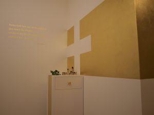 Vergoldete Wand mit weißem Kreuz und kleines Tischchen davor