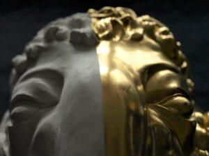 Vergoldeter Widderkopf aus Gips, Blattgold, Ölvergoldung. Eine Hälfte Gold, die andere unbehandelter Gips. Detail. GOLDSACHS