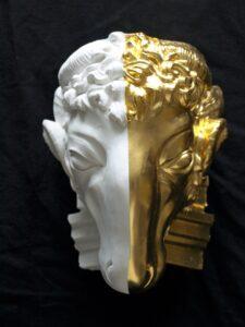 Vergoldeter Widderkopf aus Gips, Blattgold, Ölvergoldung. Eine Hälfte Gold, die andere unbehandelter Gips. GOLDSACHS